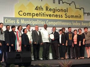 Mr. Jesus I. Barrera of Cavite Provincial Planning and Development Office together with his staff receives the award as second most competitive province in the country. Left (2nd) to center: Calabarzon RDC Vice-Chairperson and NEDA Region IV-A Dir. Luis G. Banua, Ms. Marina V. Manalo of DTI Region IV-A, former PSA Region IV-A Dir. Rosalinda P. Bautista, Regional Competitiveness Committee Chairperson and DTI Region IV-A Dir. Marilou Q. Toledo, National Competitiveness Committee Co-Chairperson Mr. Guillermo M. Luz, DTI Sec. Ramon N. Lopez and USAID Representative Dr. Stephen Andoseh.